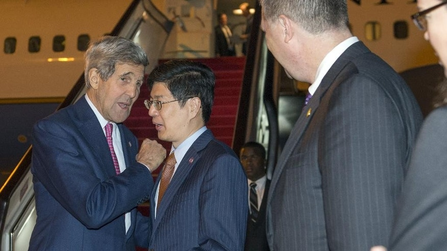 U.S. Secretary of State John Kerry, left, talks with China's Ministry of Foreign Affairs Director General Cong Peiwu as Kerry disembarks from his airplane after arriginrrival at Beijing International Airport in Beijing, Saturday, May 16, 2015. Kerry is in China to press Beijing to halt increasingly assertive actions it is taking in the South China Sea that have alarmed the United States and China's smaller neighbors. (AP Photo/Saul Loeb, Pool)