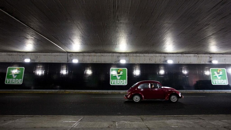In this April 6, 2015 photo, a car drives past a Green Party advertisement in a underpass in Mexico City, Mexico. To intellectuals and activists calling for its dissolution, the Green Party is nothing more than a front for the PRI, as the ruling party is called, and further proof the president's party is abiding by an old playbook. (AP Photo/Eduardo Verdugo)