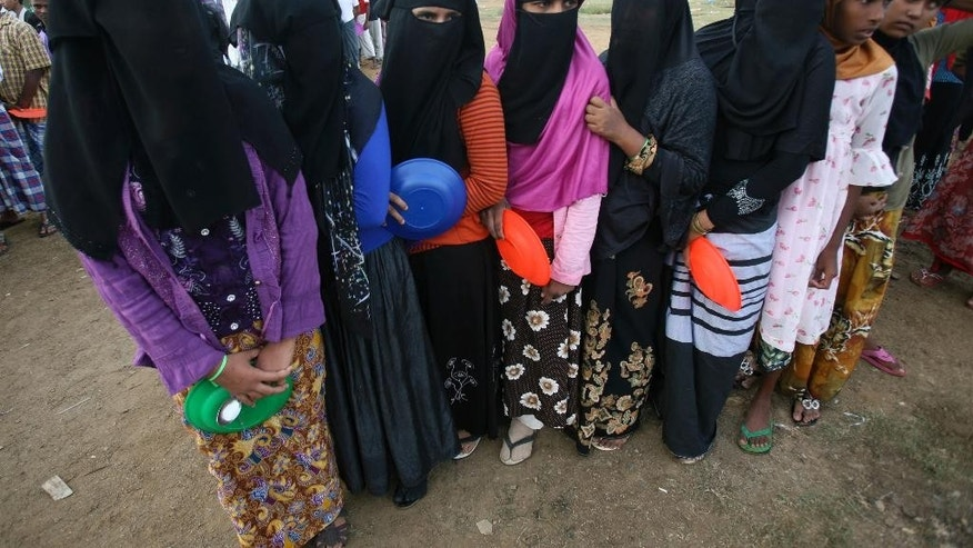 Veiled Muslim Rohingya women queue up for their meals during breakfast time at a temporary shelter in Lapang, Aceh province, Indonesia, Friday, May 15, 2015. Several thousand refugees from Bangladesh and Myanmar - fleeing either poverty or persecution - are believed to be adrift on boats in the Andaman Sea in what has become a spiraling humanitarian crisis. In recent days, about 2,000 landed in Malaysia and Indonesia, but both countries then said they could not accept any more. (AP Photo/Binsar Bakkara)