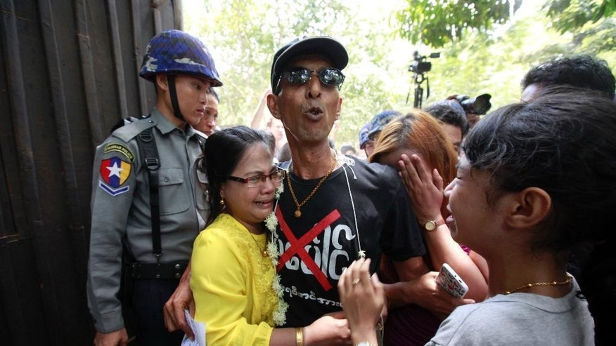 Activist Than Shwe, center, who protested in front of the Chinese Embassy in Yangon against a Chinese-backed copper mine project, is hugged by crying members of his family as he is escorted by Myanmar police officers upon arrival for his trial at a township court Friday, May 15, 2015, in Yangon, Myanmar. The court imposed new sentences with hard labor for six prominent activists who are already serving prison terms for their political activities. All six faced charges including disrupting public tranquility, deterring a public officer from carrying out his duty and for rioting and violating a peaceful assembly law for protesting outside the embassy last year. (AP Photo/Khin Maung Win)