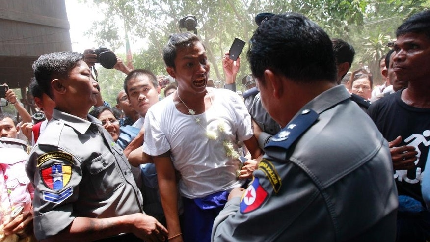 Activist Tin Htut Paing, center, who protested in front of the Chinese Embassy in Yangon against a Chinese-backed copper mine project, shouts as he is escorted by Myanmar police officers to his trial at a township court Friday, May 15, 2015, in Yangon, Myanmar. The court imposed new sentences with hard labor for six prominent activists who are already serving prison terms for their political activities. All six faced charges including disrupting public tranquility, deterring a public officer from carrying out his duty and for rioting and violating a peaceful assembly law for protesting outside the embassy last year. (AP Photo/Khin Maung Win)