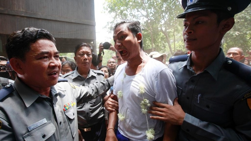 Activist Tin Htut Paing, center, who protested in front of the Chinese Embassy in Yangon against a Chinese-backed copper mine project, is escorted by Myanmar police officers to his trial at a township court Friday, May 15, 2015, in Yangon, Myanmar. The court imposed new sentences with hard labor for six prominent activists who are already serving prison terms for their political activities. All six faced charges including disrupting public tranquility, deterring a public officer from carrying out his duty and for rioting and violating a peaceful assembly law for protesting outside the embassy last year. (AP Photo/Khin Maung Win)