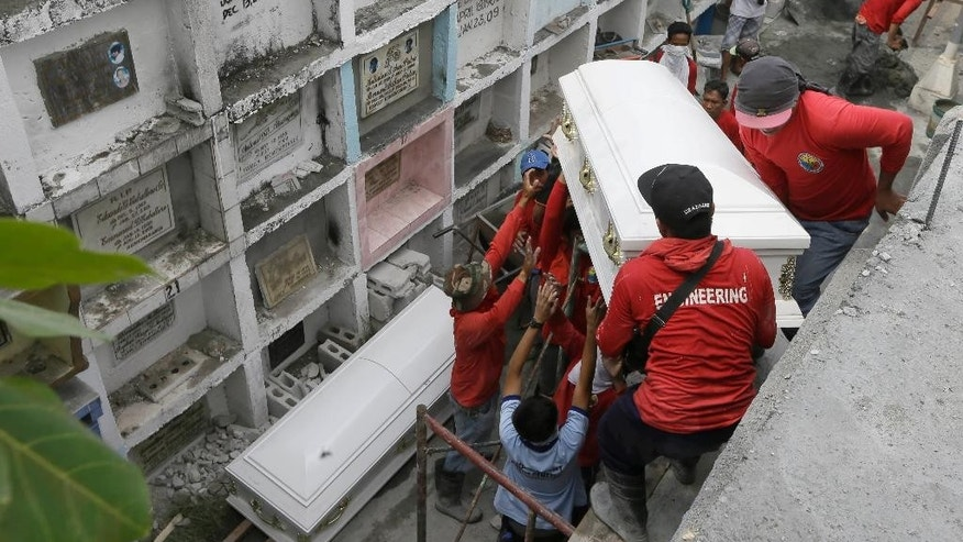 Workers slides the coffin of one of the fire victims into apartment type-crypts during a mass interment Friday, May 15, 2015 at a public cemetery in Valenzuela city, a northern suburb of Manila, Philippines. Police will open a criminal investigation into the fire incident at Kentex rubber slipper factory as a relative of several of the victims said the blaze had trapped workers in the building's second floor where iron grills on windows prevented their escape. (AP Photo/Bullit Marquez)