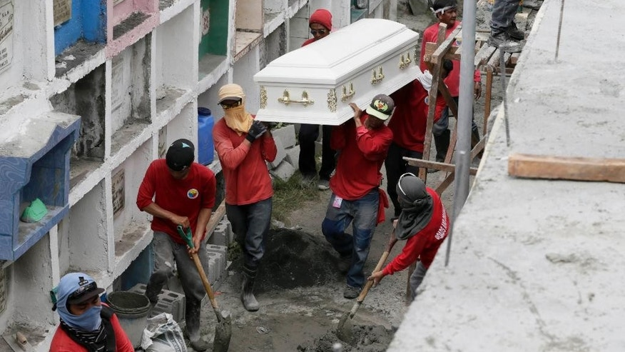 Workers carry the coffin of one of fire victims for mass interment into apartment type-crypts Friday, May 15, 2015 at a public cemetery in Valenzuela city, a northern suburb of Manila, Philippines. Police will open a criminal investigation into the fire incident at Kentex rubber slipper factory as a relative of several of the victims said the blaze had trapped workers in the building's second floor where iron grills on windows prevented their escape. (AP Photo/Bullit Marquez)