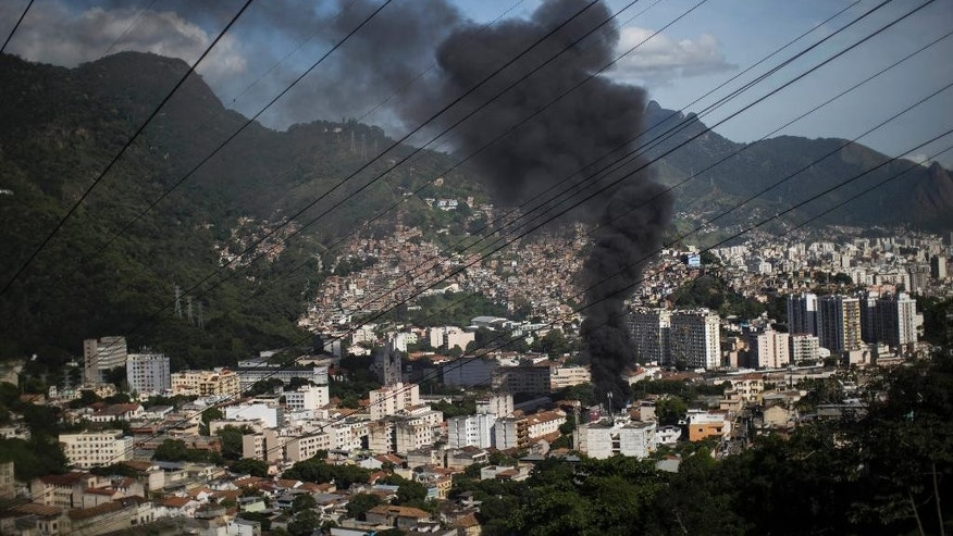 Smoke from a bus set on fire by protesters billows from downtown, seen from the Sao Carlos slum complex where the bodies of two men were found in Rio de Janeiro, Brazil, Friday, May 15, 2015. Residents of violence-wracked slums near downtown torched two buses and set up barricades of flaming tires on a main thoroughfare in anger over the deaths of the two young men. (AP Photo/Felipe Dana)