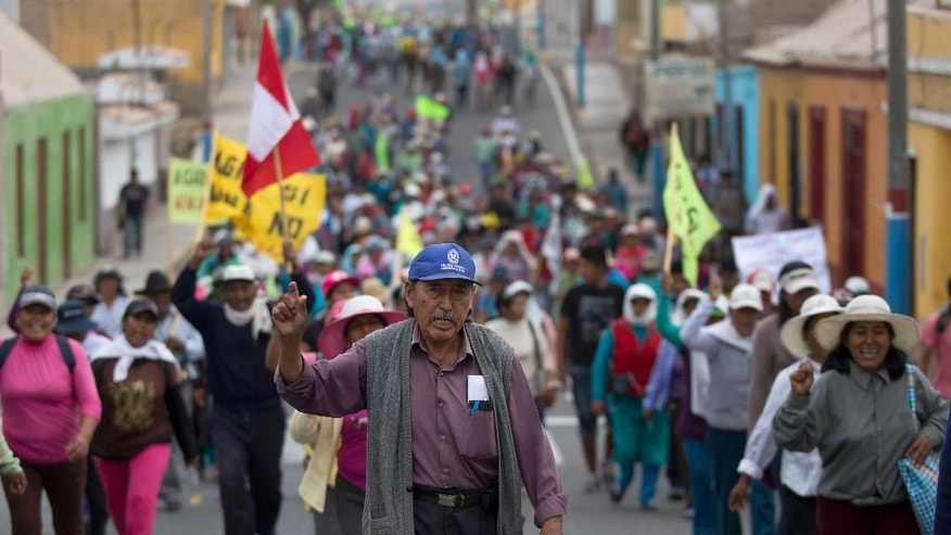 Farmers opposed to a mining project march in Cocachacra, Peru, Friday, May 15, 2015. Farmers and local leaders fear the $1.3 billion Tia Maria open-pit mine will contaminate irrigation water in the rice farming-rich Tambo valley on Peru's desert coast. Thousands have mobilized against the project, which is owned by Southern Peru Copper Corp., a subsidiary of Grupo Mexico. (AP Photo/Martin Mejia)