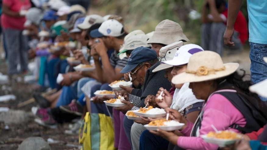 Farmers opposed to a mining project stop for lunch as they protest in Cocachacra, Peru, Friday, May 15, 2015. Farmers and local leaders fear the $1.3 billion Tia Maria open-pit mine will contaminate irrigation water in the rice farming-rich Tambo valley on Peru's desert coast. Thousands have mobilized against the project, which is owned by Southern Peru Copper Corp., a subsidiary of Grupo Mexico. (AP Photo/Martin Mejia)