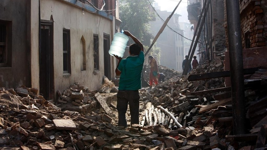 A Nepalese man carrying a water jar walks past damaged houses in Bhaktapur, Nepal, Thursday, May 14, 2015. The past three weeks have been misery for Nepal. On April 25, a magnitude-7.8 earthquake killed thousands of people, injured tens of thousands more and left hundreds of thousands homeless. Then, just as the country was beginning to rebuild, a magnitude-7.3 earthquake battered it again. (AP Photo/Bikram Rai)