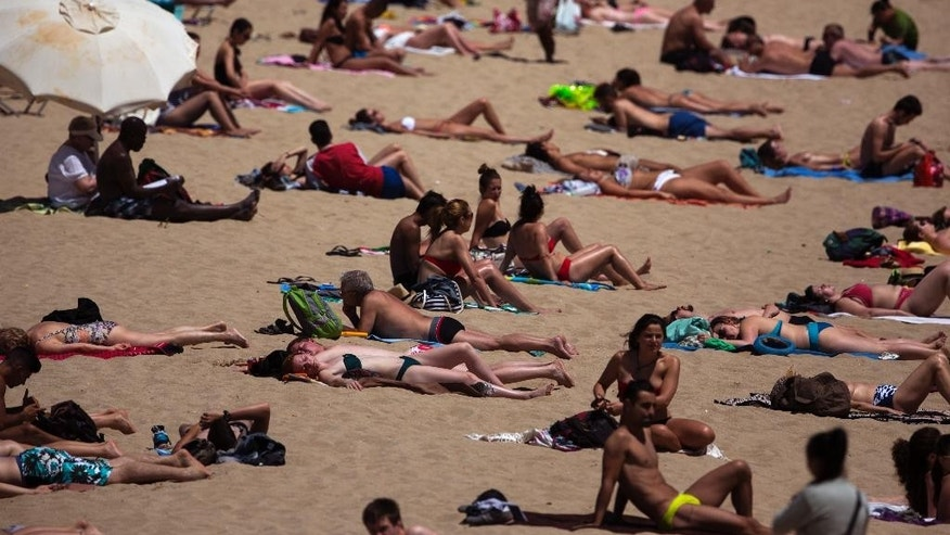 People sunbathe in a beach in Barcelona, Spain, Friday, May 15, 2015. The Iberian Peninsula has experienced record high temperatures for May as thermometers shot up to levels normally only seen in midsummer. (AP Photo/Emilio Morenatti)