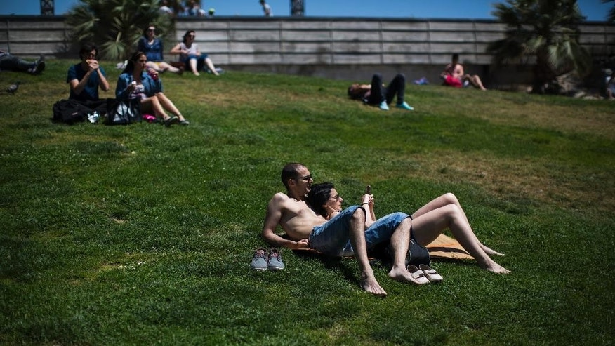 People sunbathe in a public park in Barcelona, Spain, Friday, May 15, 2015. The Iberian Peninsula has experienced record high temperatures for May as thermometers shot up to levels normally only seen in midsummer. (AP Photo/Emilio Morenatti)