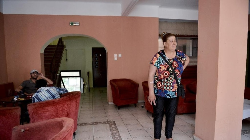In this photo taken on Thursday, May 14, 2015 Dia Kasam from Syria stands in the hotel where she stays,  in the northern Greek port city of Thessaloniki. As Europe struggles to hammer out ground rules to distribute asylum seekers among its members, refugees are left to deal with the chaotic _ and costly _ reality of fleeing from war. (AP Photo/Giannis Papanikos)