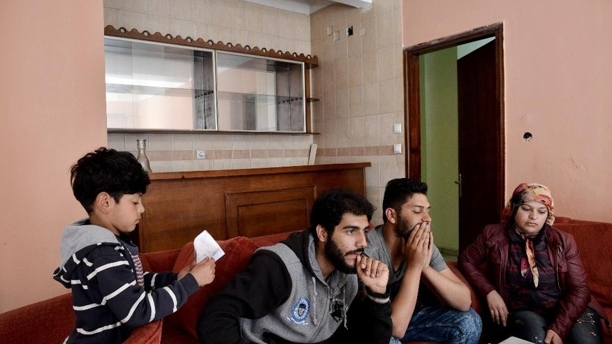 In this photo taken on Thursday, May 14, 2015 Mohamed, second left, his son Mosab, left, and Syrian Derkam, second right, with his Iraqi wife sit in a hotel, in the northern Greek port city of Thessaloniki. As Europe struggles to hammer out ground rules to distribute asylum seekers among its members, refugees are left to deal with the chaotic _ and costly _ reality of fleeing from war. (AP Photo/Giannis Papanikos)