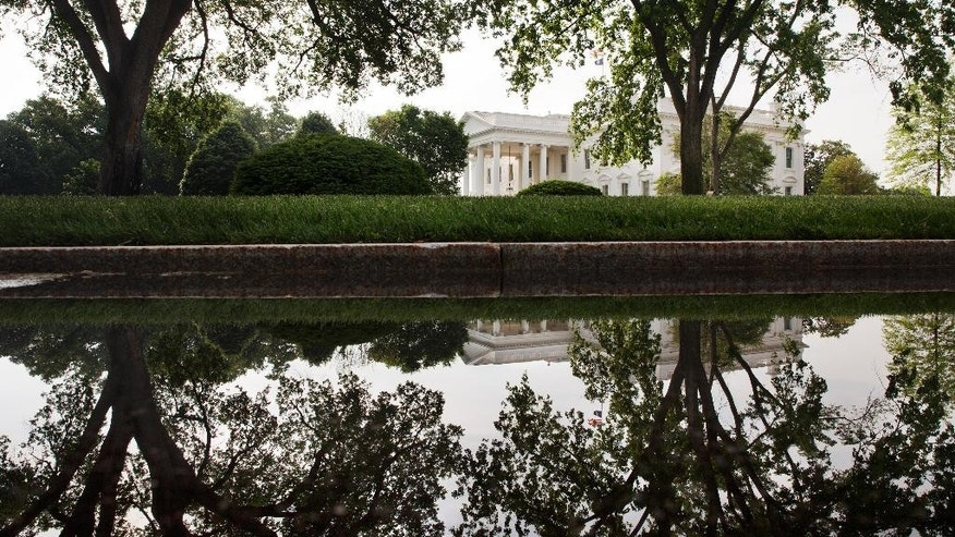 The White House and trees are reflected in a puddle on the White House complex, Saturday, May 16, 2015, in Washington. The Pentagon says U.S. commandos have mounted a rare raid in eastern Syria, killing the Islamic State commander in charge of oil fields in a firefight and capturing his wife.  (AP Photo/Jacquelyn Martin)