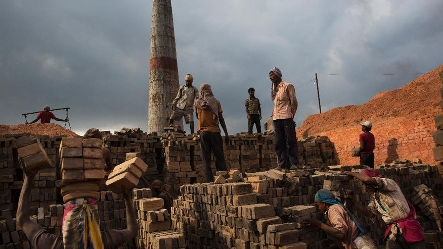 In this Wednesday, May 13, 2015 photo, Indian and Nepalese laborers work at a brick factory in Bhaktapur, Nepal. Nepal, facing billions in reconstruction costs, has appealed for foreign governments and agencies to help with aid and funds. Almost 745,600 buildings and homes have been damaged or destroyed, including at least 87,700 in the capital, according to Nepal's emergency authority. Engineers say only 40 percent of Kathmandu's damaged buildings as habitable. (AP Photo/Bernat Amangue)