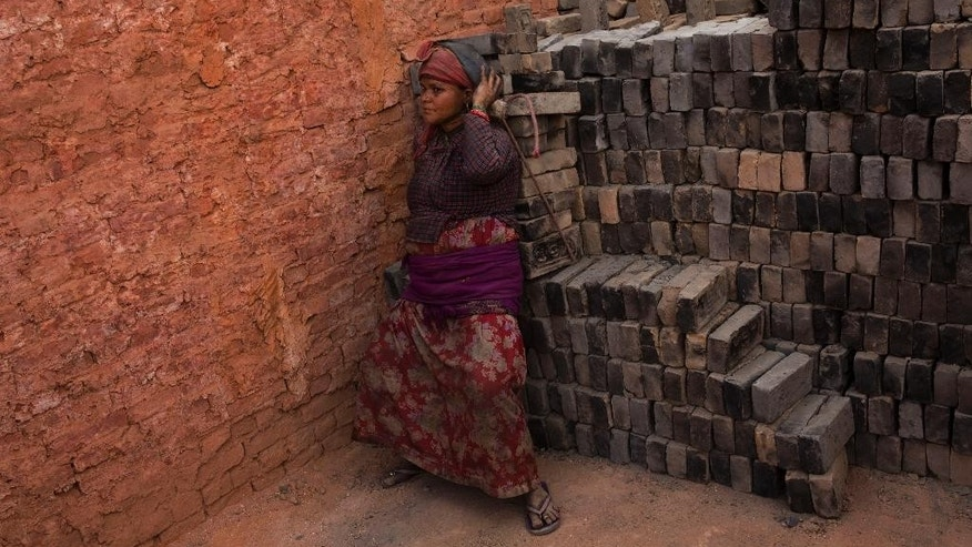 In this Wednesday, May 13, 2015 photo, a Nepalese laborer carries a load of bricks at a brick factory in Bhaktapur, Nepal. Nepal, facing billions in reconstruction costs, has appealed for foreign governments and agencies to help with aid and funds. Almost 745,600 buildings and homes have been damaged or destroyed, including at least 87,700 in the capital, according to Nepal's emergency authority. Engineers say only 40 percent of Kathmandu's damaged buildings as habitable. (AP Photo/Bernat Amangue)