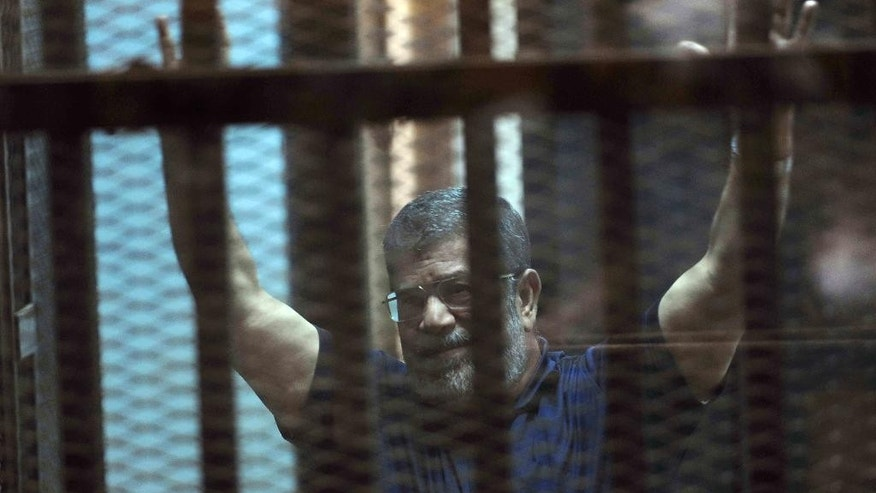 Ousted Egyptian President Mohammed Morsi raises his hands as he sits behind glass in a courtroom, in a converted lecture hall in the national police academy in an eastern Cairo suburb, Egypt, Saturday, May 16, 2015. An Egyptian court on Saturday sentenced ousted President Mohammed Morsi to death over his part in a mass prison break that took place during the 2011 uprising that toppled Hosni Mubarak. (AP Photo/Ahmed Omar)