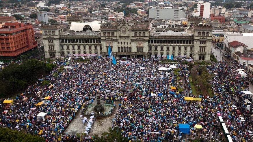 Protesters gather outside the National Palace to demand the resignation of Guatemalan President Otto Perez Molina in Guatemala City, Saturday, May 16, 2015. The protest comes after Perez Molina's Vice President, Roxana Baldetti, resigned on Friday, May 8, amid a corruption scandal involving what prosecutors allege was a multimillion-dollar scheme in which bribes were paid to avoid customs duties on imports. Baldetti's private secretary is being singled out by authorities as the alleged ringleader of the scheme, but Baldetti has not been charged and denies any involvement.  (AP Photo/Moises Castillo)