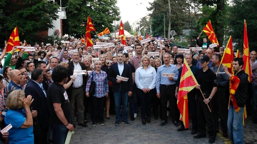 "People carrying national flags and small banners reading ""Thank you heroes"" sing the national anthem in front of a police station in Skopje, Tuesday, May 12, 2015.  Some hundreds of people marched peacefully in Skopje on Tuesday, honoring 8 police officers who were killed over the weekend during the fighting with an armed group in Macedonian northern town of Kumanovo. (AP Photo/Boris Grdanoski)"