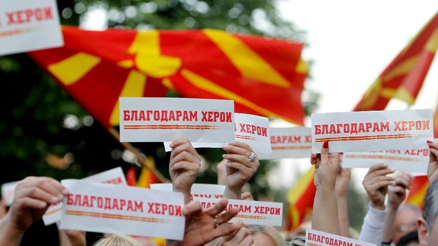"People march through a street carrying national flags and small banners reading ""Thank you heroes"" in Skopje, Tuesday, May 12, 2015. Hundreds of people marched peacefully in Skopje on Tuesday, honoring 8 police officers who were killed over the weekend during fighting with an armed group in Macedonian northern town of Kumanovo. (AP Photo/Boris Grdanoski)"