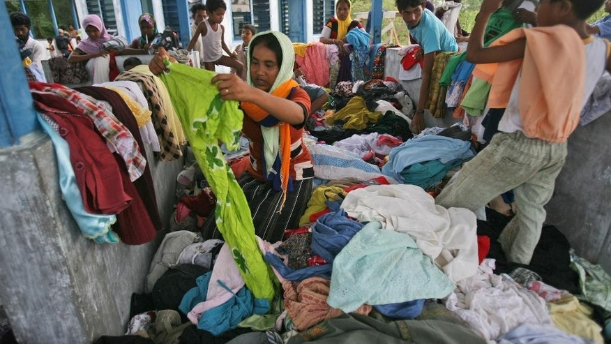 Ethnic Rohingya migrants sift through used clothing donated by local residence at a temporary shelter in Langsa, Aceh province, Indonesia, Saturday, May 16, 2015. More than 1,000 people fleeing persecution in Myanmar and poverty in Bangladesh landed in several places in Southeast Asia, describing killings, extortion and near-starvation after a harrowing journey at sea. (AP Photo/Binsar Bakkara)