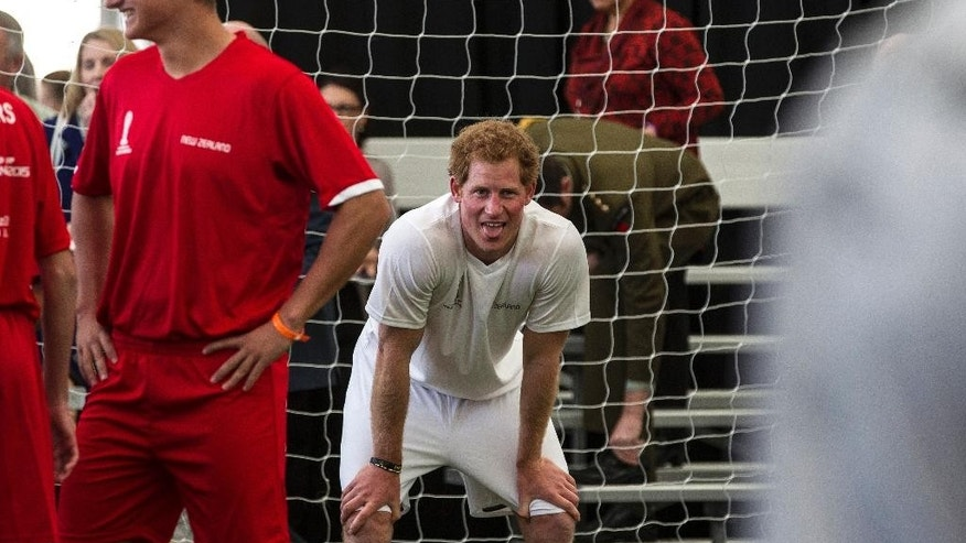 Britain's Prince Harry, center, sticks his tongue out during a 5-a-side football game at The Cloud, a multi-purpose venue in Auckland, New Zealand, Saturday, May 16, 2015. Prince Harry is on the last day of his visit to New Zealand. (Michael Craig/Herald on Sunday via AP) NEW ZEALAND OUT, AUSTRALIA OUT