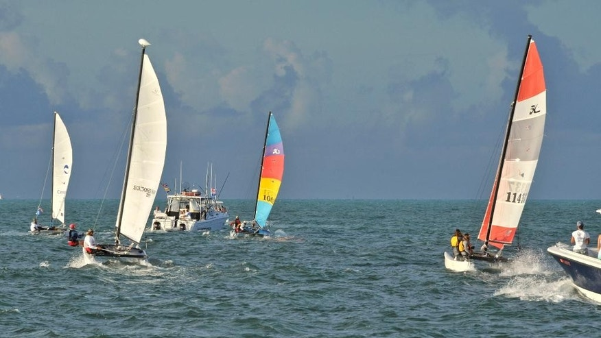 In this photo provided by the Florida Keys News Bureau, Hobie Cat sailboats and support boats head towards Havana after departing Key West, Fla., Saturday, May 16, 2015. Five 16-foot-long Hobie Cats are participating in the the Havana Challenge, believed to be the first U.S. government-sanctioned sailing race between Key West and Cuba in more than 50 years. (Bert Budde/Florida Keys News Bureau via AP)