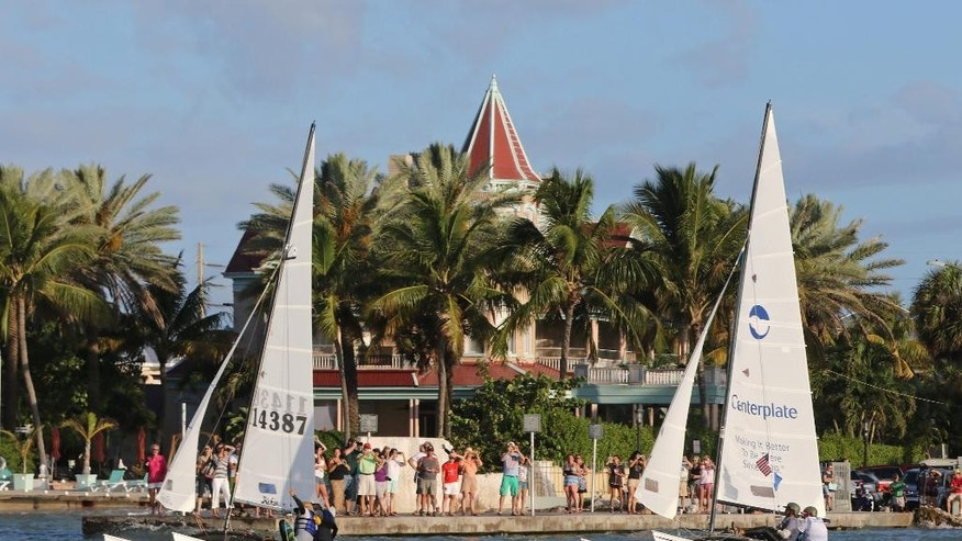 In this photo provided by the Florida Keys News Bureau, crews aboard two16-foot-long Hobie Cat sailboats sail past the Southernmost House in Key West, Fla., Saturday, May 16, 2015, just after the start of a more than 90-mile race to Havana, Cuba. The Havana Challenge is believed to be the first U.S. government-sanctioned sailing race between Key West and Cuba in more than 50 years. Five Hobie Cats are participating in the event. (Rob O'Neal/Florida Keys News Bureau via AP)