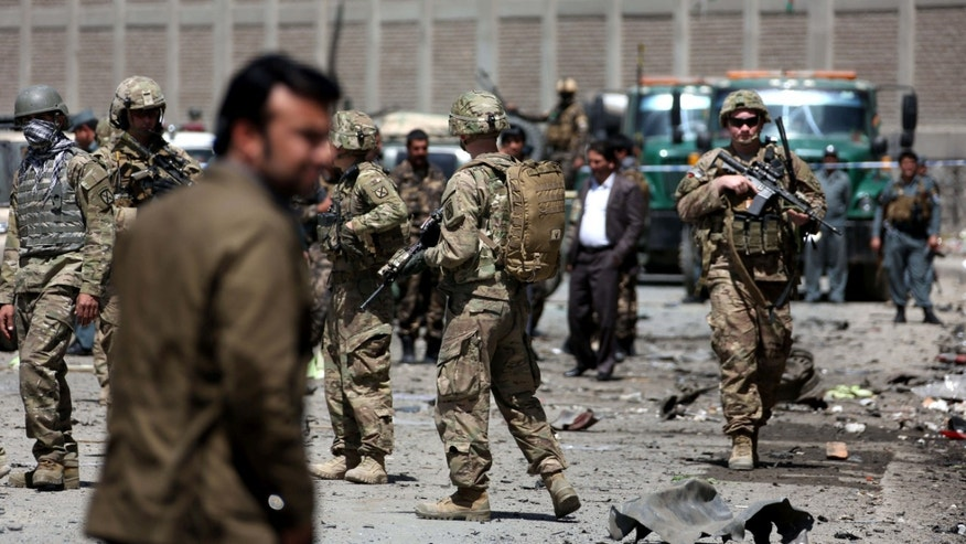 May 17, 2015: US forces and Afghan security inspect the site after a suicide bombing attack near Kabul's international airport in Kabul, Afghanistan.