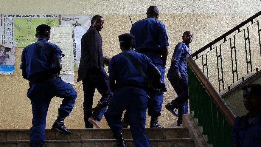 General Nijungeko Juvenal, who took part in the fizzled coup attempt, is brought handcuffed to the court after surrendering in  Bujumbura, Burundi, Saturday  May 16, 2015. Topless, barefoot and with wounds from alleged torture seventeen security officials, including five generals appeared before a prosecutor who is expected to file treason charges against them over the attempted coup of President Pierre Nkurunziza, lawyers of some of the suspects said Saturday. (AP Photo/Jerome Delay)