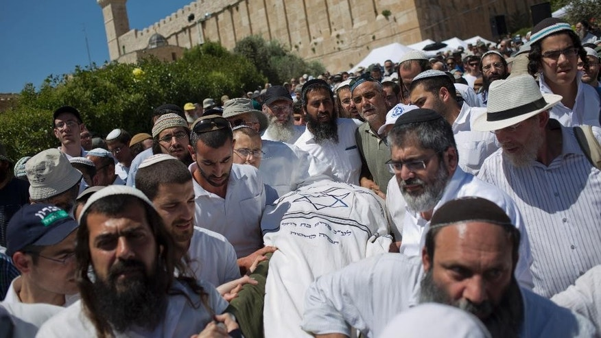 Jewish settlers carry the body of Rabbi Moshe Levinger during his the funeral outside Hebron's holiest site, known to Jews as the Tomb of the Patriarchs and to Muslims as the Ibrahimi Mosque, in the Jewish settlement in Hebron, West Bank, Sunday, May 17, 2015. Levinger, a leading figure in Israel's settler movement, was laid to rest Sunday in Hebron, where he helped establish a controversial Jewish community after Israel captured the territory from Jordan in the 1967 Mideast war. (AP Photo/Ariel Schalit)