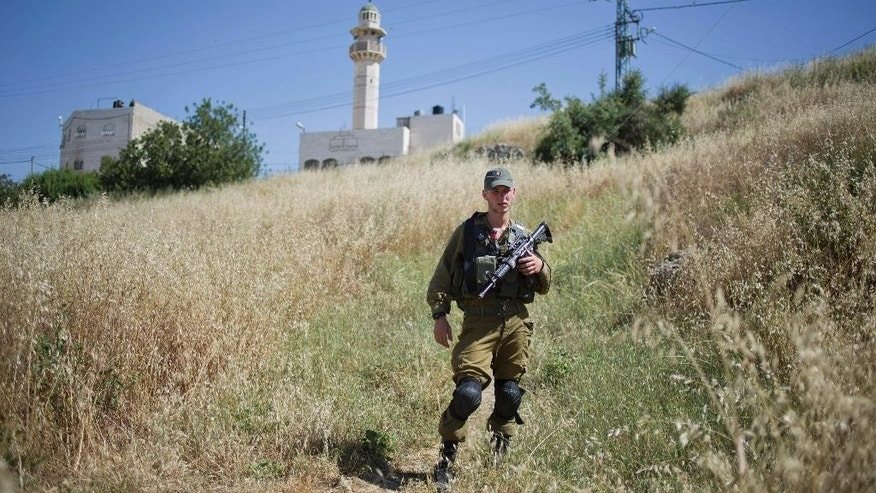 An Israeli soldier secures the old Jewish cemetery during the funeral of Rabbi Moshe Levinger in the Jewish settlement in Hebron, West Bank, Sunday, May 17, 2015. Levinger, a leading figure in Israel's settler movement, was laid to rest Sunday in Hebron, where he helped establish a controversial Jewish community after Israel captured the territory from Jordan in the 1967 Mideast war. (AP Photo/Ariel Schalit)