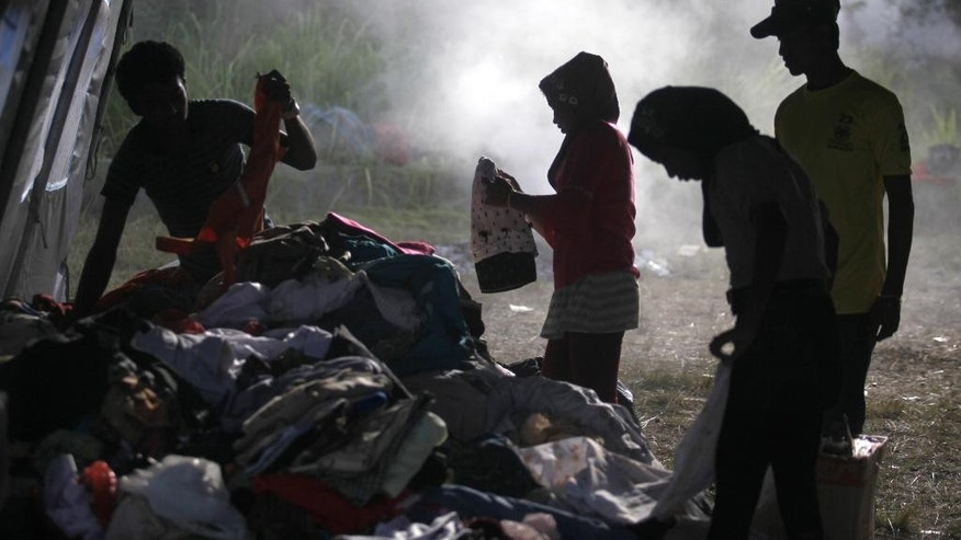 Ethnic Rohingya migrants sift through used clothing donated by local residents at a temporary shelter in Langsa, Aceh province, Indonesia, Sunday, May 17, 2015. Boats filled with more than 2,000 desperate and hungry people have landed in Indonesia, Malaysia and Thailand, and thousands more migrants are believed to be adrift at sea after a crackdown on human traffickers prompted captains and smugglers to abandon their human cargo. (AP Photo/Binsar Bakkara)