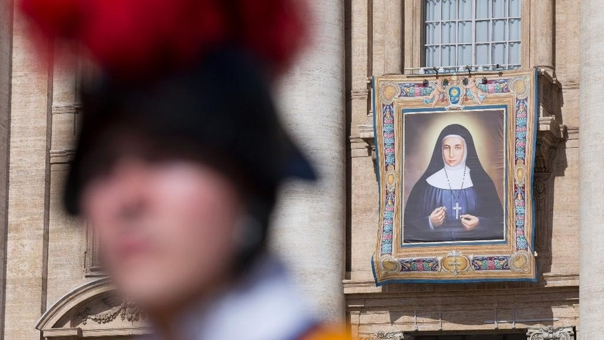 The tapestry of St. Marie Alphonsine Ghattas  hangs from a balcony in St. Peter's Square at the Vatican prior to the start of the canonization ceremony led by Pope Francis Sunday, May 17, 2015. The pontiff will canonize two 19th-century nuns from what was then Ottoman-ruled Palestine. The new saints, Mariam Bawardy and Marie Alphonsine Ghattas, are the first from the region to be canonized since the early days of Christianity.(AP Photo/Alessandra Tarantino)