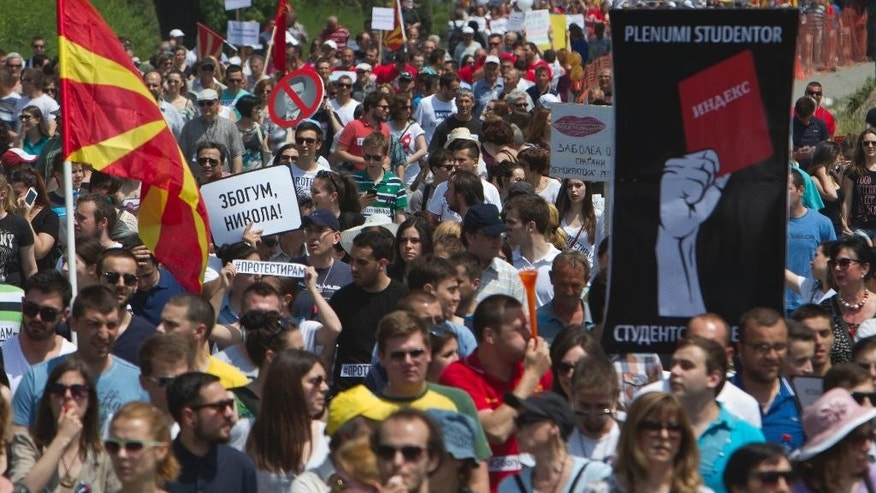 "Protesters holding a Macedonian flags and banners reading ""Resignation"" and ""Goodbye Nikola"" protest against Prime Minister Nikola Gruevski as they march towards the offices of Macedonia's conservative government, in capital Skopje on Sunday, May 17, 2015.  Some thousands of people are gathered in the centre of Skopje to demand the resignation of Gruevski, amid a series of alleged scandals including corruption, wiretapping and cover ups, but Gruevski rejects the accusations. (AP Photo/Visar Kryeziu)"
