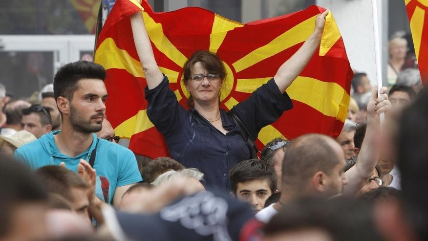 A woman holds Macedonian flag during a protest in front of the Government building in Skopje, Macedonia, on Sunday, May 17, 2015. Macedonian opposition started massive demonstrations Sunday in Skopje protesting against the conservative government of the Prime Minister Nikola Gruevski, demanding its resignation. (AP Photo/Boris Grdanoski)