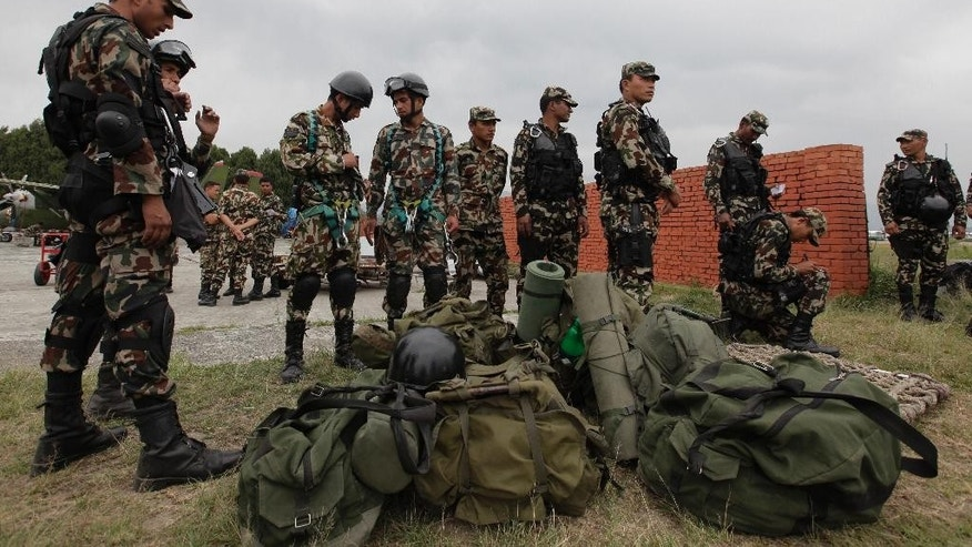 FILE - In this Friday, May 15, 2015, file photo, Nepalese army soldiers prepare to leave for a rescue mission to the site where the suspected wreckage of a U.S. Marine helicopter, that disappeared earlier this week while on a relief mission in the earthquake-hit Himalayan nation, was spotted, in Kathmandu, Nepal. Nepalese rescuers on Friday found three bodies near the wreckage of the chopper that was carrying six Marines and two Nepalese army soldiers. (AP Photo/Niranjan Shrestha, File)
