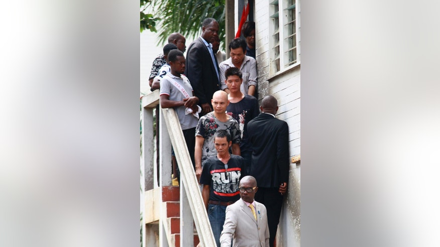 Plain clothes police officers accompany Chinese nationals accused of illegal mining out  of a courtroom, following a hearing in Accra, Ghana, Monday May 18, 2015. Authorities say 10 Chinese nationals accused of illegal mining in Ghana now face firearms charges in court. Justice Francis Obiri on Monday granted the subjects $12,000 bail each and adjourned the case until a hearing later this month. Each of the defendants is accused of illegal firearms possession, and they pleaded not guilty to the charges through an interpreter in court. (AP Photo/Christian Thompson)