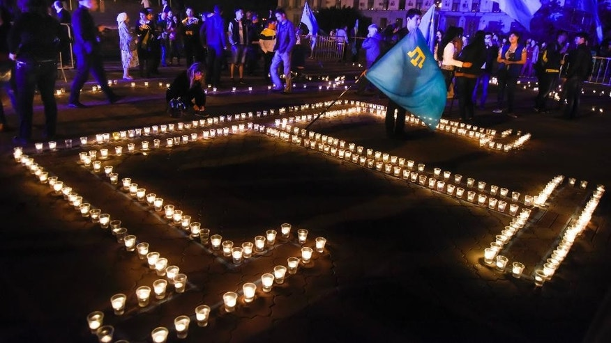 "In this photo taken on Sunday, May  17, 2015, in Simferopol, Crimea, young Tatars with the Crimean Tatars blue flags light candles in a form of their Crimean Tartar peoples' symbol during a rally requiem "" Light a flame in my heart "" to commemorate the 71st anniversary of Soviet dictator Stalin's mass 1944 deportation of Crimean Tatars. (AP Photo/ Alexander Polegenko)"