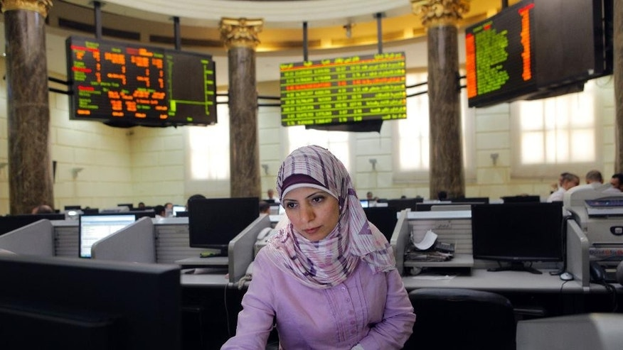 FILE - In this Tuesday, June 26, 2012 file photo, an Egyptian trader checks a monitor at the Egyptian Exchange in Cairo, Egypt. On Monday, May 18, 2015, Egypt's government suspended a tax imposed on the market's capital gains for two years, causing shares to rise in early trading. (AP Photo/Amr Nabil, File)