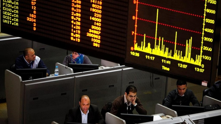 FILE -- In this Jan. 21, 2013 file photo, Egyptian traders work at the stock market in Cairo, Egypt. Egypt's government on Monday, May 18, 2015, suspended a tax imposed on the market's capital gains, for two years causing shares to rise in early trading. The suspension comes nearly a year after President Abdel-Fattah el-Sissi approved the law, which put 10 percent tax on capital gains that fueled a sell-off by investors. Some investors went to courts to abolish government's law.  (AP Photo/Amr Nabil, File)