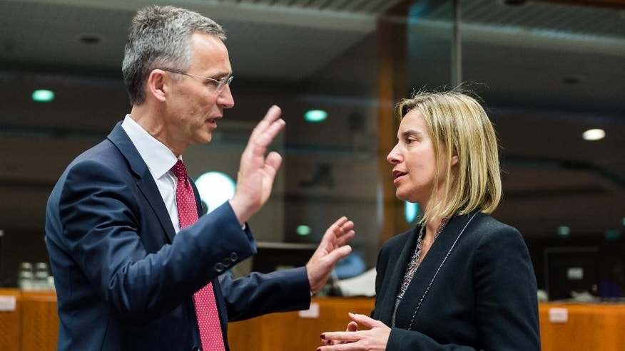 NATO Secretary General Jens Stoltenberg, left, talks with European Union High Representative Federica Mogherini during a meeting with EU defense and foreign ministers at the European Council building in Brussels on Monday May 18, 2015. A European Union naval operation to go after the trafficking networks that send thousands of migrants across the Mediterranean into Europe could be launched in the coming weeks and NATO stands ready to help if needed, officials said Monday during a meeting of EU foreign and defense ministers. (AP Photo/Geert Vanden Wijngaert)