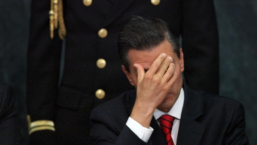 FILE - In this Wednesday, Jan. 21, 2015, file photo, Mexico's President Enrique Pena Nieto attends a ceremony promoting housing for low income families, single mothers and members of the armed forces at Los Pinos presidential residence in Mexico City. Pena Nieto has also seen his pro-business agenda derailed by allegations of corruption and the disappearance of 43 students after they were handed over by police to local drug traffickers. (AP Photo/Marco Ugarte, File)
