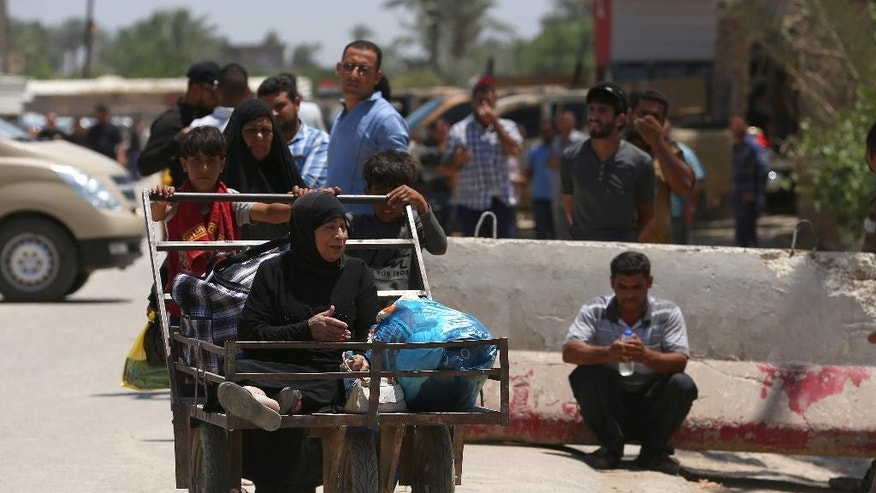 "In this Saturday, May 16, 2015 photo, Iraqis fleeing from their hometown of Ramadi walk on a street near the Bzebiz bridge, 65 kilometers (40 miles) west of Baghdad. Muhannad Haimour, a spokesman for the governor of Iraq's Anbar province, said Sunday, ""Ramadi has fallen,"" to the Islamic State group. He also said the military's operational command in the city has been taken as well. (AP Photo/Hadi Mizban)"