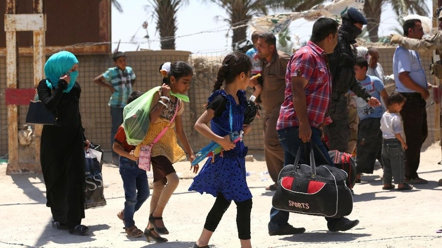 In this Saturday, May 16, 2015 photo, Iraqis fleeing from their hometown of Ramadi, Iraq, walk on a street near the Bzebiz bridge, 65 kilometers (40 miles) west of Baghdad. The Islamic State group seized control of the city of Ramadi on Sunday, sending Iraqi forces racing out of the city in a major loss despite the support of U.S.-led airstrikes targeting the extremists. (AP Photo/Hadi Mizban)