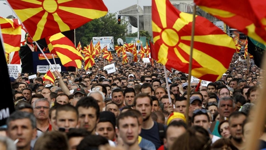 People wave national flags during a protest in front of the Government building in Skopje, Macedonia, on Sunday, May 17, 2015. Macedonian opposition started massive demonstrations Sunday in Skopje protesting against the conservative government of the Prime Minister Nikola Gruevski, demanding its resignation. (AP Photo/Boris Grdanoski)