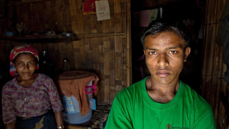 In this In this Tuesday, May 12, 2015, photo Mohammad Tayub, right a 14-year-old who returned to his home in village of Thetkabyin, North of Sittwe, western Rakhine State, Myanmar, explains how he was forcibly held for 12 days on a trafficking boat. Tayub says he was shoved onto the wooden vessel with hundreds of other Rohingya Muslims, some fleeing persecution and others like himself tricked by brokers who made money by turning him into a migrant. He describes sitting with his knees bent into his chest, pressed up against other sweaty bodies in the cabin's rancid heat, while members of the crew hit anyone who made a sound with iron rods and belts. (AP Photo/Gemunu Amarasinghe)