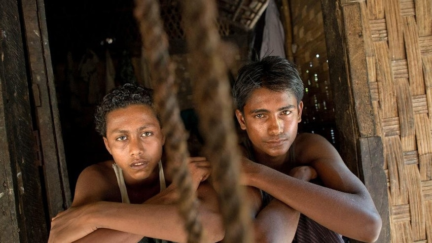 In this Monday, May 11, 2015, photo 16-year-old Sadik Hussein, left, and 17-year-old Noor Alam, hours after returning to their homes in Thetkabyin Village, north of Sittwe, western Rakhine state, Myanmar. They say they escaped from a human trafficking boat, where they sat for days with their knees bent into their chest, pressed up against other sweaty bodies in the cabin's rancid heat. They say members of the crew paced back and forth with iron rods and belts, hitting anyone who dared speak or even vomit from the nauseating stench and rolling waves. (AP Photo/Gemunu Amarasinghe)