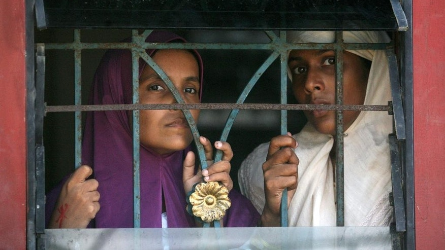 Ethnic Rohingya looks out from inside a temporary shelter in Langsa, Aceh province, Indonesia, Monday, May 18, 2015. Boatloads of more than 2,000 migrants — ethnic Rohingya Muslims fleeing persecution in Myanmar and Bangladeshis trying to escape poverty — have landed in Indonesia, Malaysia and Thailand in recent weeks. Aid groups estimate that thousands more are stranded at sea after a crackdown on human traffickers prompted captains and smugglers to abandon their human cargo. (AP Photo/Binsar Bakkara)