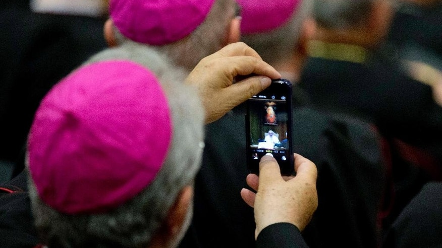 A bishop photographs Pope Francis as he delivers his speech during the opening session of a Italian Episcopal Conference meeting, at the Vatican, Monday, May 18, 2015. (AP Photo/Alessandra Tarantino)