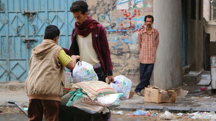 May 6, 2015 - A Yemeni volunteer, center, provides food items as a boy takes an item from the cart to his family in Taiz, Yemen. The country has endured shortages of food, water, medicine and electricity as a result of a Saudi-led blockade. Humanitarian organizations had been scrambling to distribute aid before the end of the truce.